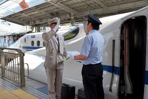 新大阪駅の新幹線ホームで引き継ぎをする夏服姿のJR東海の運転士(左)と、半袖シャツのJR西日本の運転士