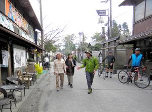「復興支援ツアー」で松永辰博さん(左から3人目)が観光客を阿蘇神社の門前町に案内した=9日、熊本県阿蘇市、後藤たづ子撮影