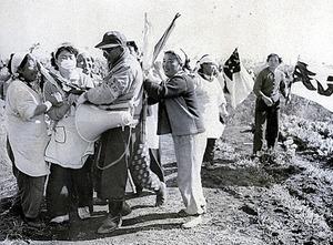 米軍立川基地拡張のため農地の強制測量に入った測量員を、笑顔で阻止しようとする農家の主婦たち=1955年11月