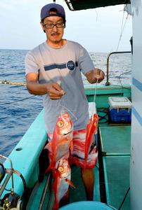 キンメダイを釣りあげた小椋康介さん。漁は夜明けとともに始まる=神津島沖