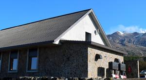 望岳台に完成した防災シェルター。右奥の十勝岳からは噴気が上がっていた=美瑛町