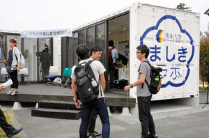 2台のコンテナハウスを「く」の字に置き、木の縁側でつなげた「ましきラボ」。開所式には熊本大の学生も駆けつけた=益城町寺迫