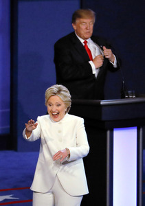 米ラスベガスで19日、最後の米大統領選候補者テレビ討論会を終え、共和党のトランプ氏(奥)の前を笑顔で通り過ぎる民主党のクリントン氏=AP