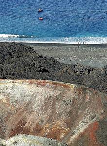 西之島に上陸する研究者たち。手前は噴火口=20日午前8時25分、東京都小笠原村、本社機から、杉本康弘撮影