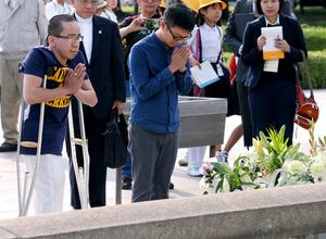 慰霊碑に献花し、手を合わせるドクさん(左)と歌手のハイチュウさん=20日午後、広島市中区の平和記念公園、上田幸一撮影