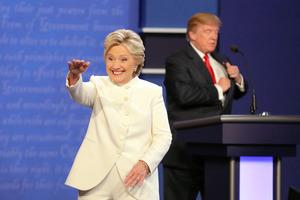 米ラスベガスで19日、最後の米大統領選候補者討論を終え、ノートをしまい込む共和党のトランプ氏(奥)と、聴衆に笑顔で手を振る民主党のクリントン氏=AP