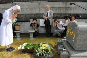 墓前祭では、「平和を」という文字が刻まれた墓に参加者が献花し、手を合わせた=長崎市石神町