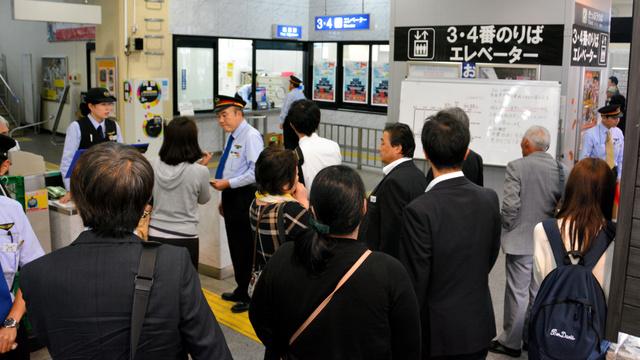 運転見合わせについて、JR松江駅の係員に尋ねる利用客ら=21日午後3時前
