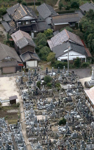 住宅の屋根瓦が崩れ、墓石が倒れていた=21日午後4時27分、鳥取県倉吉市、朝日新聞社機から、川村直子撮影