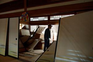 自宅を片付ける吉村俊治さん(74)。築70年を超える家の柱が折れて傾いた。「祖父の代から住んできたが建て直すしかない」と肩を落とした=22日午前8時27分、鳥取県北栄町、小玉重隆撮影