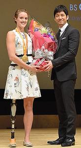 フォーラムでは、番組のナレーターを務める俳優の西島秀俊さん(右)が、エリー・コール選手に花束を渡した