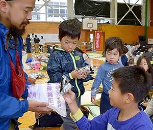 朝食のおにぎりを手にする子どもたち=22日午前7時26分、鳥取県倉吉市の河北小学校体育館、高橋孝二撮影