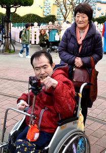 東京ディズニーランドを訪れた胎児性水俣病患者の半永一光さん。風景や人々にカメラを向けた=3月25日、千葉県浦安市、同行者撮影