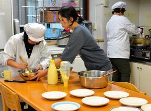 職員の手伝いを受け、夕食を作る利用者の女性たち=志布志市