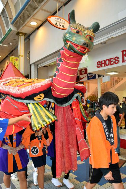 子どもたちに運ばれる亀蛇(愛称ガメ)=八代市の本町商店街