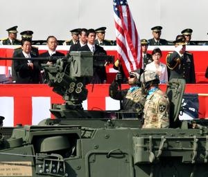 自衛隊記念日の式典に参加した米陸軍の装甲車両を観閲する安倍晋三首相(左端)ら=23日午後、陸上自衛隊朝霞訓練場、仙波理撮影
