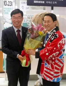 第1便で到着したエアソウルの柳光熙社長(左)を出迎える平井知事=境港市佐斐神町