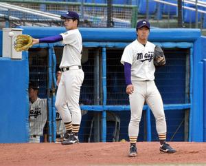 ブルペンで投球練習をする明大の柳(右)=角野貴之撮影