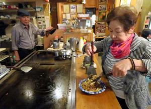 鉄板で焼いた焼きそばを皿にもる「オモニ」の高姫順さんと夫の梁幸道さん=大阪市生野区、中野晃撮影