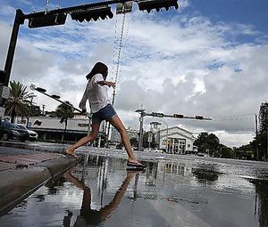排水溝から逆流した水で冠水した交差点。女性が恐る恐る水たまりに足を踏み入れた=16日、いずれもマイアミビーチ、矢木隆晴撮影