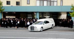 多くの参列者がひつぎを乗せた車を見送った=25日午後3時21分、福岡市南区、伊藤繭莉撮影