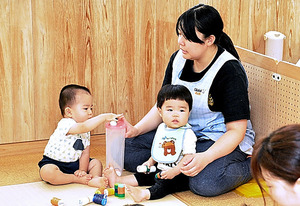 東京都内の認可保育所。0歳児クラスでは保育士が見守るそばで子どもたちが遊んでいた