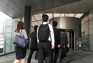 過労自殺した新入社員の労災認定を受け、電通の本社に立ち入り調査に入る労働基準監督官ら=14日、東京都港区