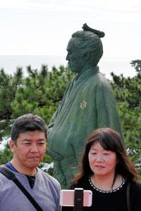龍馬像を背景に「自撮り」する観光客