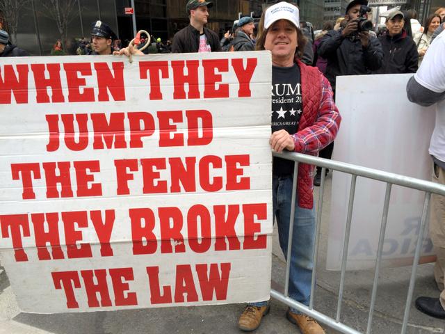 写真①トランプ氏への抗議者に囲まれながら、「トランプは正しい」と反論する建設作業員ウィデルさん。「フェンス(国境)を乗り越えた時、彼らは法を破ったのだ」とのプラカードを掲げていた=3月19日、ニューヨーク・マンハッタン5番街、金成隆一撮影