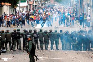 カラカスで26日、マドゥロ大統領の退陣を求めるデモで治安部隊と衝突する参加者たち=ロイター