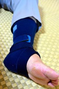 女性の左足は特にしびれが強くサポーターが欠かせないという=長崎市香焼町