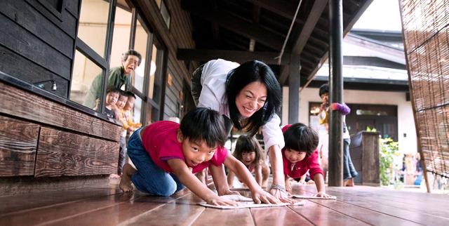 どろんこ保育園で子どもたちと一緒に廊下を雑巾がけ。競争になり思わず笑顔がこぼれる=埼玉県朝霞市