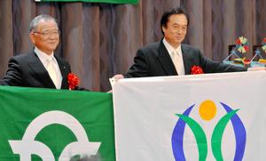 それぞれの市と町の旗を交換した大橋良一・埼玉県加須市長(左)と伊沢史朗・福島県双葉町長=福島県いわき市