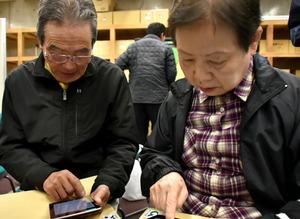スマートフォンを使って安否情報を入力する訓練の参加者=広川町広