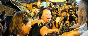 催涙スプレーを警察にかけられて目があけられなくなった女性=6日、香港、益満雄一郎撮影