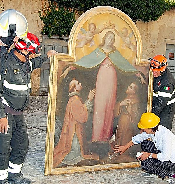 イタリア中部ノルチャで1日、被災した教会から消防士が運び出した絵画。伊消防局提供=AP