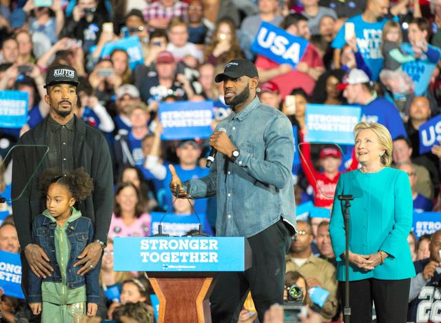 米オハイオ州クリーブランドで6日、米大統領選の集会でバスケットボール選手のレブロン・ジェームズさん(中央)の応援演説を聞く民主党のクリントン候補(右)=AP