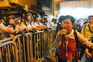 警官隊の前で大声をあげるデモの参加者=7日未明、香港、益満雄一郎撮影