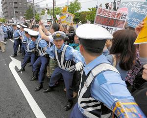 ヘイトスピーチデモを阻止しようとする人たちと県警の警察官たち=6月5日、川崎市中原区、杉本康弘撮影