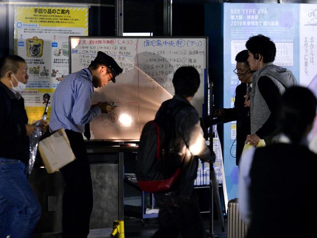 博多駅前の陥没事故の影響でJR博多駅の新幹線コンコースが停電し、ホワイトボードを使って乗り場や時刻を案内する係員たち=8日午後2時39分、福岡市博多区、福岡亜純撮影
