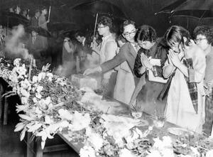 安保反対闘争の渦中で亡くなった樺美智子さんを悼み、現場に作られた祭壇で焼香する人たち=1960年6月16日、国会南門前
