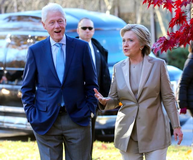 8日、米ニューヨーク州チャパクアで投票を終えた後、夫のビル・クリントン氏(左)と話すヒラリー・クリントン氏=AP