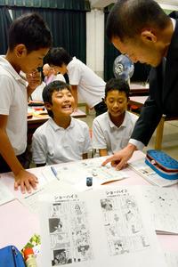 自作マンガを使った副教材で授業をする小学校教諭の樗木厚さん(右端)=大阪市生野区