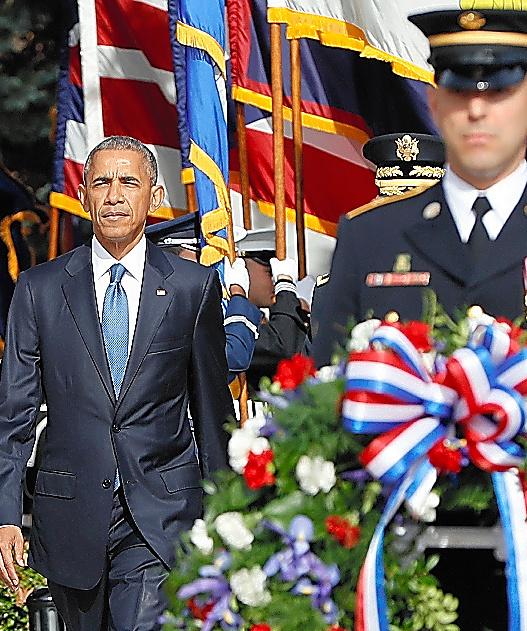 米国の祝日の「退役軍人の日」となる11日、米ワシントン郊外のアーリントン墓地であった式典に参加するオバマ米大統領(左)=AP