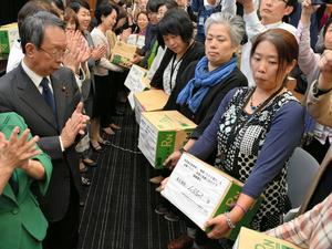 住宅支援の打ち切り反対の署名を国会議員に渡す自主避難者(右側)ら=10月26日、東京・永田町の参院議員会館、伊沢健司撮影