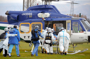 防護服を着た救急隊員らが傷病者をヘリコプターで搬送する訓練が行われた=13日午前、北海道共和町、佐久間泰雄撮影