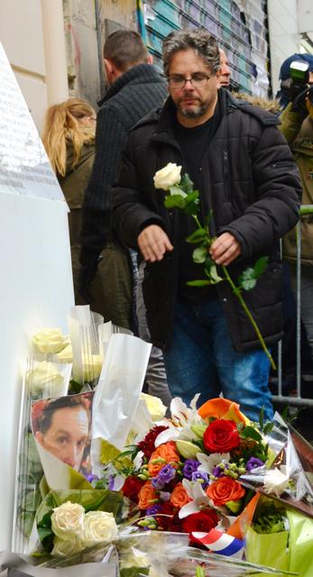 コンサートホール「ルバタクラン」での犠牲者90人の名前が刻まれたプレートの前に、花を手向ける男性=13日、パリ、青田秀樹撮影