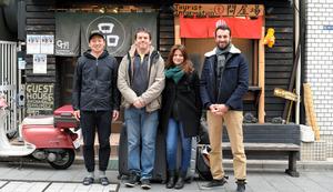 ゲストハウス品川宿をチェックアウトするフランス人旅行者とスタッフ(左端)=東京都品川区