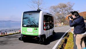 田沢湖畔の県道を自動運転で走行するバス=秋田県仙北市