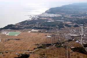 東京電力福島第一原発(中央奥)の周辺を取り囲むように広がる、中間貯蔵施設予定地=10日午前、福島県双葉町、本社機から、堀英治撮影